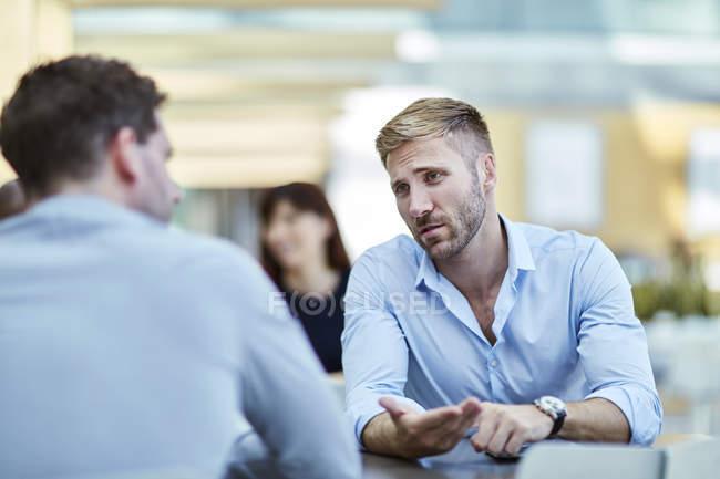 Uomo d'affari che fa gesti e parla con un collega — Foto stock