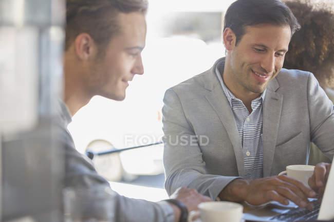 Hommes d'affaires avec café travaillant à l'ordinateur portable dans le café — Photo de stock