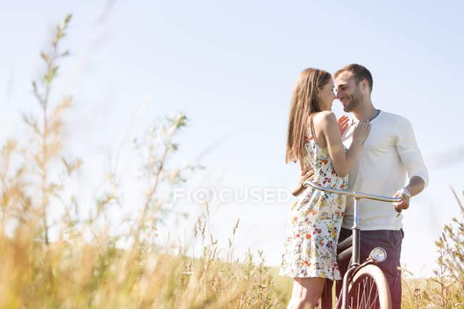 Ласковая молодая пара с велосипедными объятиями в солнечной сельской местности — стоковое фото