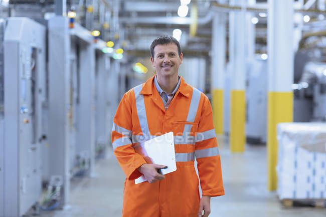 Portrait confident worker in reflective clothing with clipboard in factory — Stock Photo
