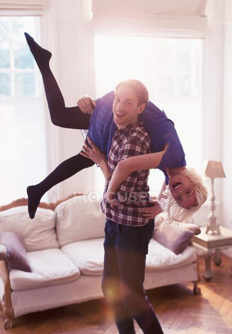 Marido juguetón retrato transportar a esposa hombro en sala de estar - foto de stock