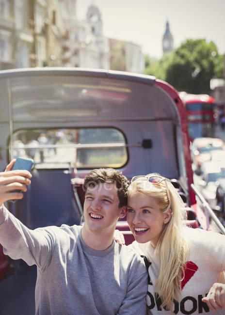 Couple taking selfie on double-decker bus in London — Stock Photo