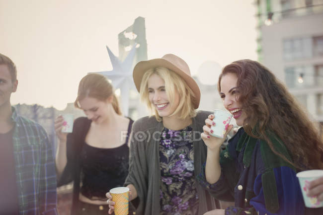 Smiling young women drinking and laughing at rooftop party — Stock Photo
