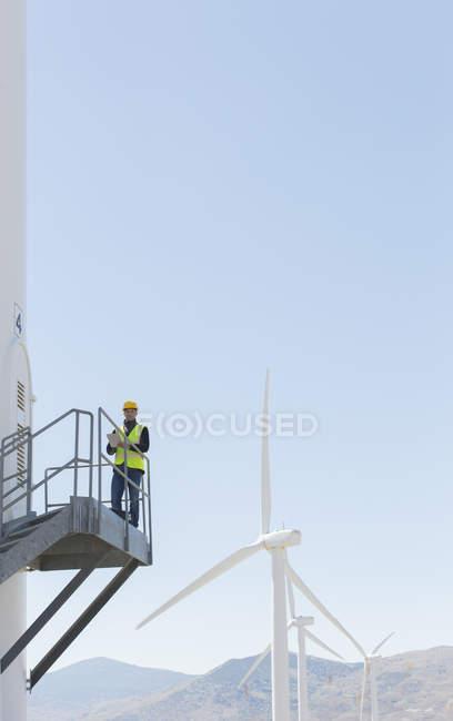 Travailleur debout sur une éolienne dans un paysage rural — Photo de stock