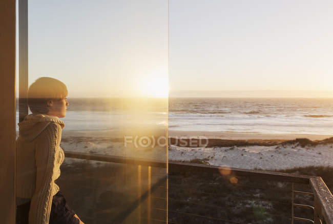 Serene woman watching sunset over ocean — Stock Photo
