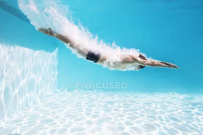 Вид сбоку человека, погрузиться в бассейн — стоковое фото