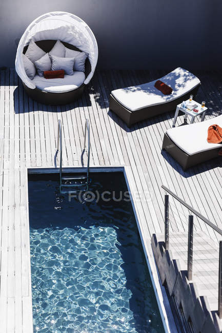 Lounge chairs on wooden deck near lap pool — Stock Photo
