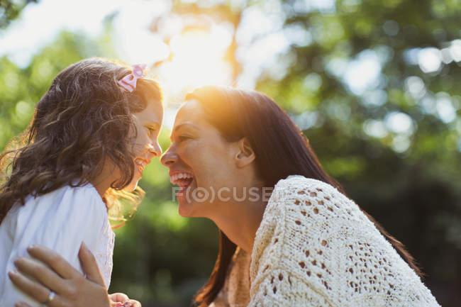 Entusiástico mãe e filha sorrindo cara a cara — Fotografia de Stock