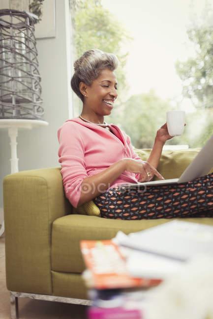 Lächelnde Reife Frau mit Laptop und Kaffeetrinken auf sofa — Stockfoto