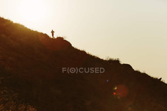 Silhouette of runner ascending hillside at sunset — Stockfoto