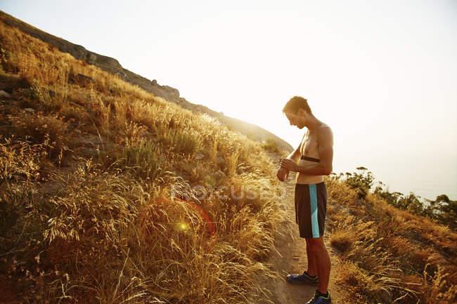 Голими грудьми чоловіки бігун на стежці перевірка смарт-годинник — стокове фото