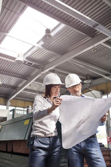 Инженеры просматривают чертежи на заводе — стоковое фото