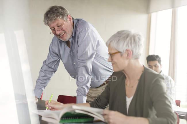 Étudiants discutant devoirs dans la salle de classe de l'éducation des adultes — Photo de stock