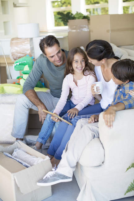 Family relaxing on sofa in new house — Stock Photo