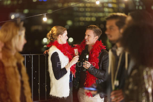 Young couple drinking champagne at nighttime rooftop party — Stock Photo