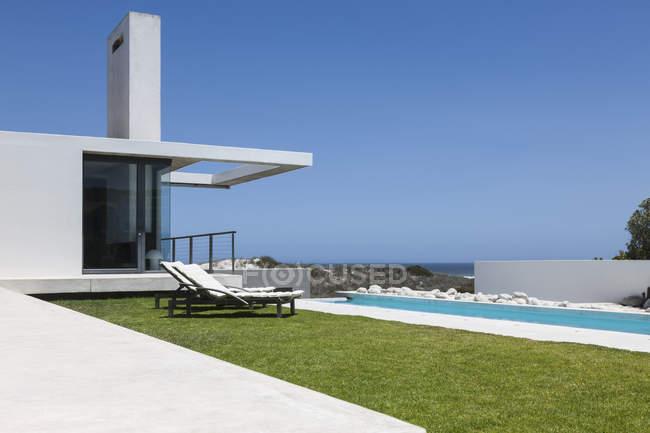 Prato e piscina sul grembo lungo casa moderna — Foto stock