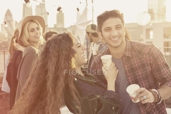 Jeunes amis adultes boire et rire à la fête sur le toit — Photo de stock