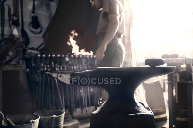 Blacksmith at fire behind anvil in forge — Stock Photo