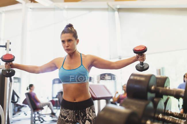 Fokussierte Frau tun Hantel Brust Fly in Turnhalle — Stockfoto