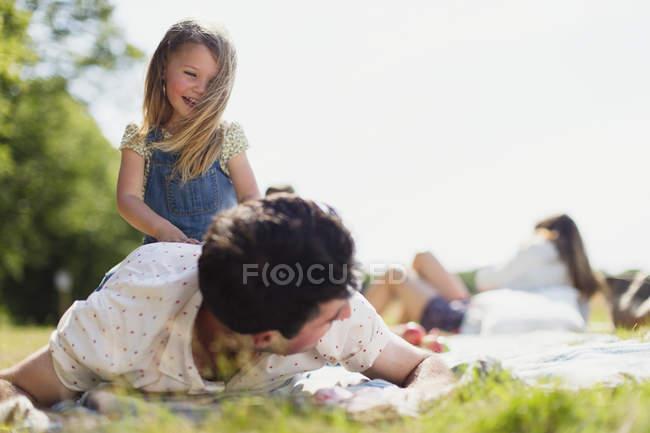 Играющая дочь на вершине отца в солнечном поле — стоковое фото