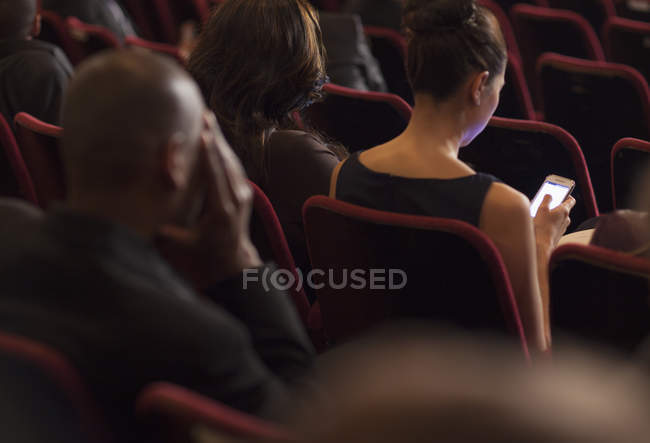 Rear view of woman using cell phone in theater audience — Stock Photo