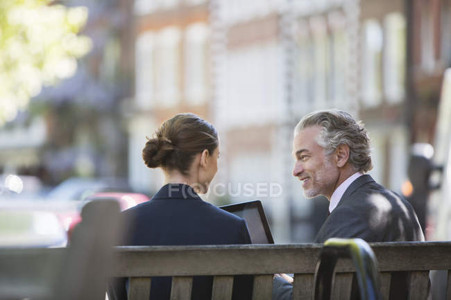 Business people talking on urban bench — Stock Photo