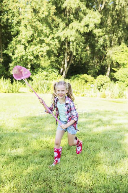 Chica jugando con la red de mariposa en el patio trasero - foto de stock