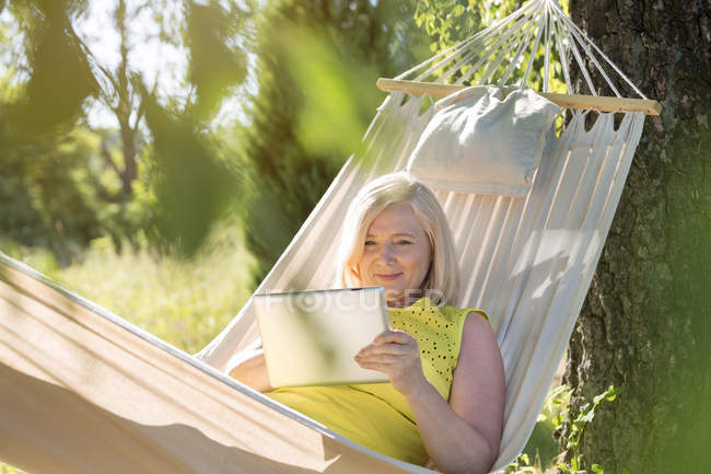 Donna anziana che utilizza tablet digitale e rilassarsi in amaca estiva — Foto stock