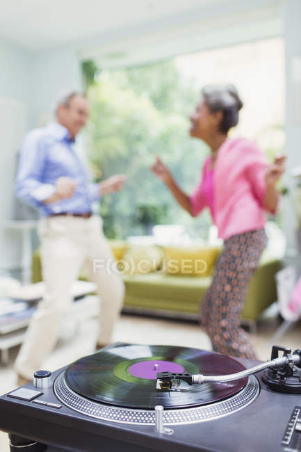 Playful nature couple dancing in living room behind record player — Stockfoto