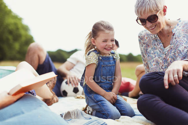 Grandmother and granddaughter laughing on blanket — Stock Photo