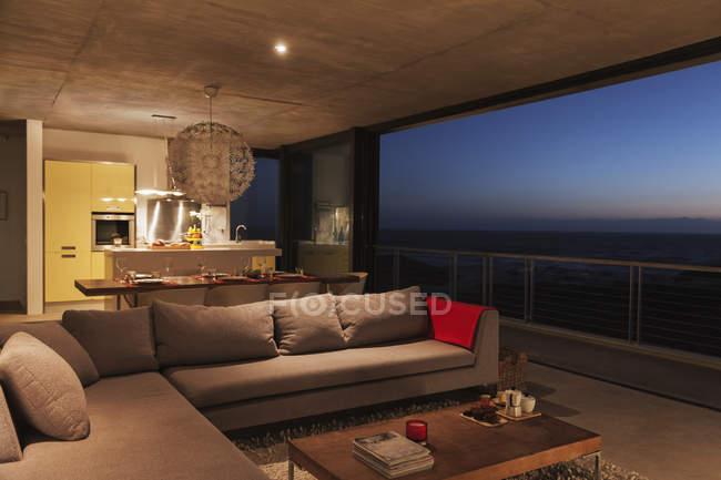 Sofa und Esstisch im modernen Wohnzimmer mit Blick auf Meer — Stockfoto