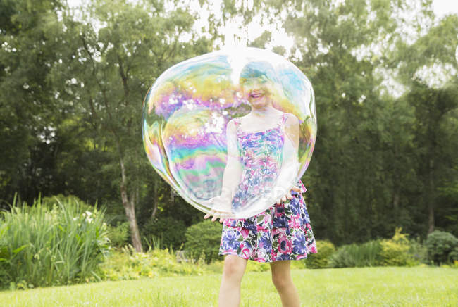 Father and daughter playing with large bubbles in backyard — Stock Photo