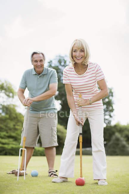Счастливая старшая пара играет в крокет — стоковое фото