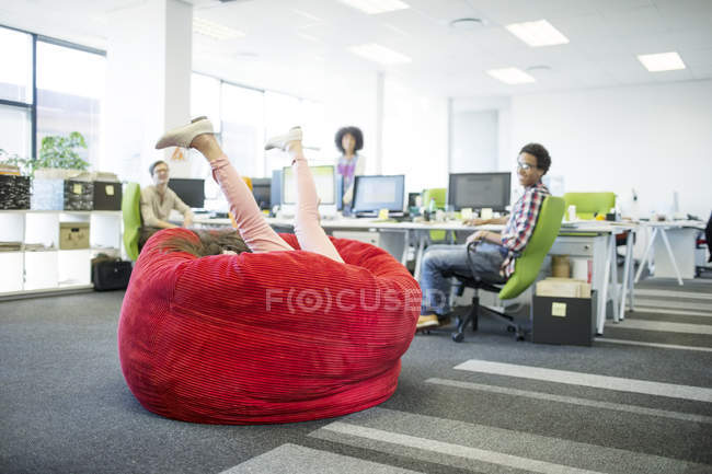 Businesswoman Playing In Beanbag Chair Office Stock Photo