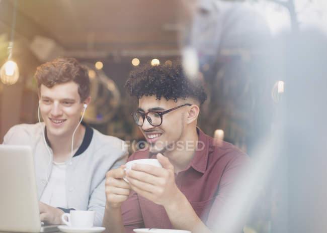 Amici che bevono caffè e usano il computer portatile nel caffè — Foto stock