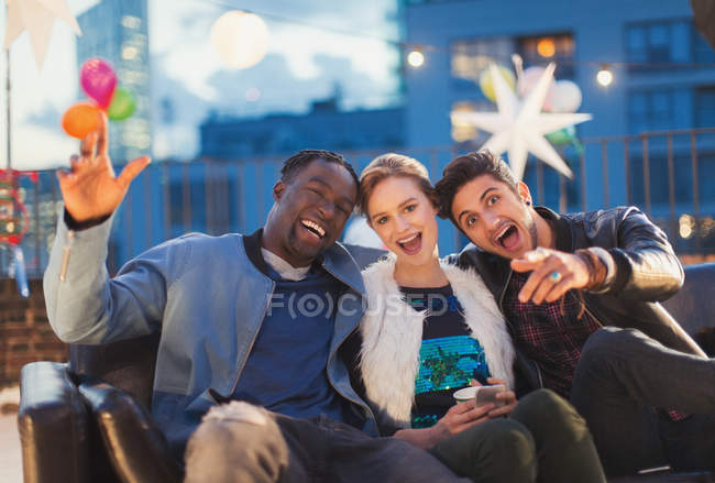Portrait enthusiastic friends enjoying rooftop party — Stockfoto