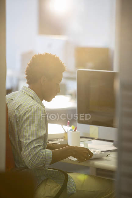 Businessman reading at desk in modern office — Stock Photo