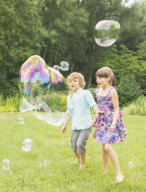 Niños jugando con burbujas en el patio trasero - foto de stock