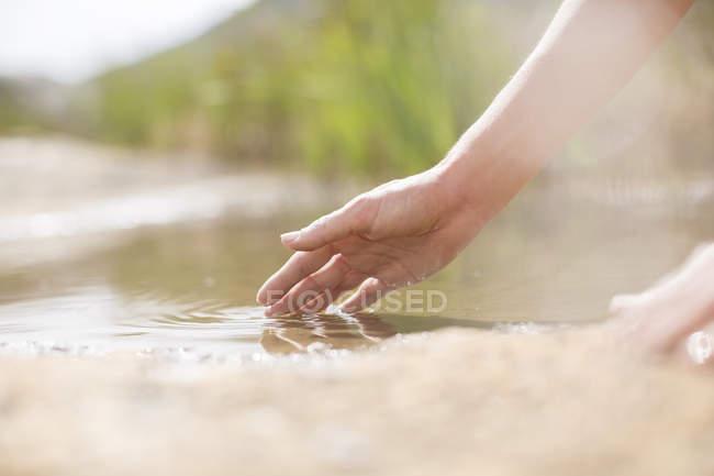 Mulher mergulhando os dedos na lagoa rural — Fotografia de Stock