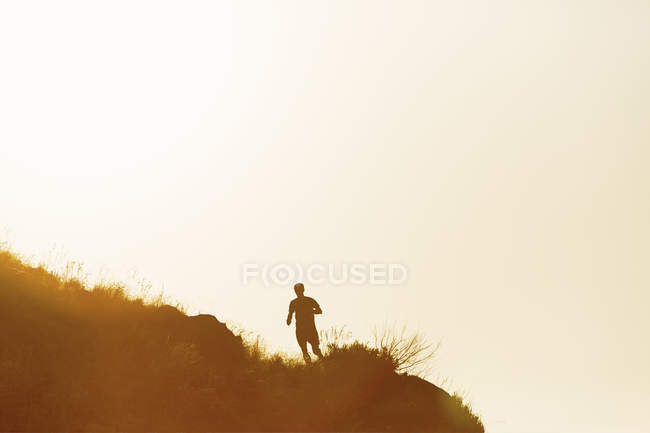 Silhouette of a man running on hill at sunset — Stock Photo