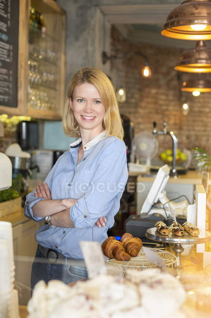 Portrait smiling cafe owner with arms crossed behind the counter — Stock Photo