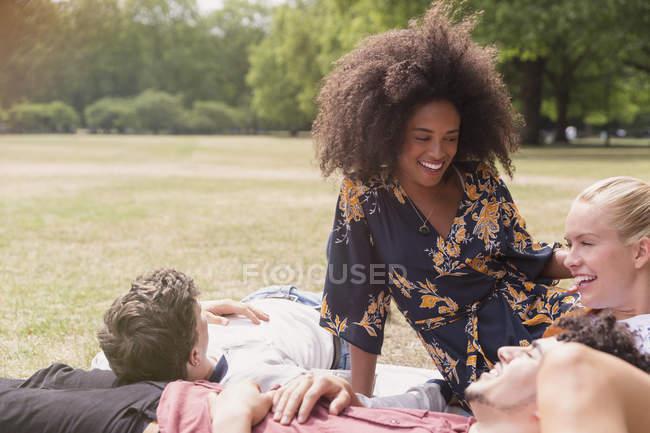 Друзья отдыхают на одеяле в парке — стоковое фото