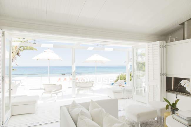 Modern living room overlooking beach and ocean — Stock Photo