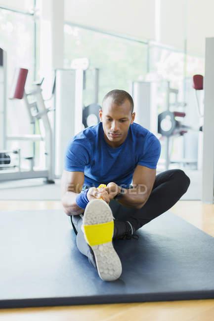 Mann mit Widerstand Band um Bein Strecken in Turnhalle — Stockfoto