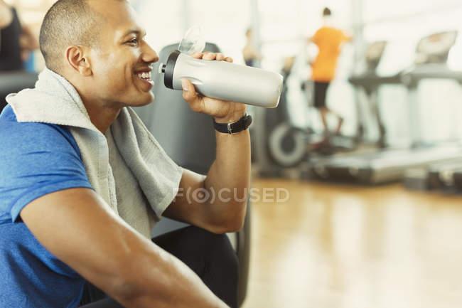 Lächelnde Menschen Trinkwasser in Turnhalle — Stockfoto