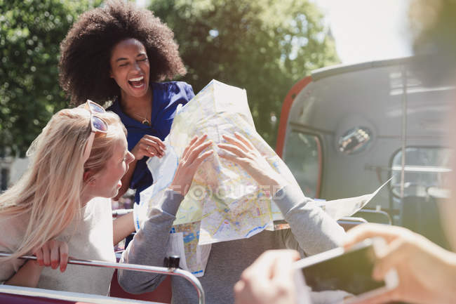 Playful friends with map on double-decker bus — Stock Photo
