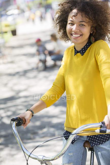 Porträt lächelnde Frau auf Fahrrad im Park — Stockfoto
