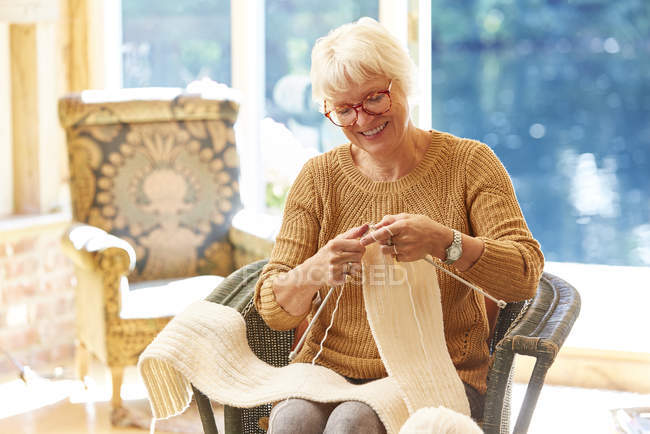 Senior woman knitting in living room — Stock Photo