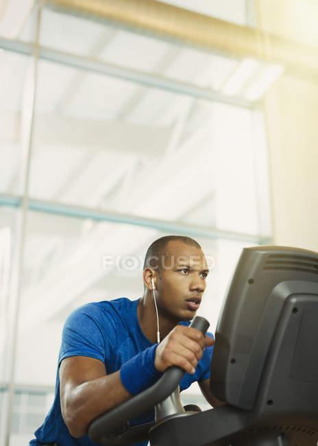 Entschlossenen Mann auf Crosstrainer im Fitnessstudio — Stockfoto