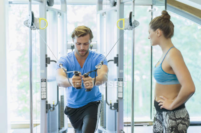 Personal trainer guiding man using cable exercise machine at gym — Stock Photo